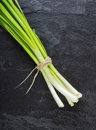 green onions: A bunch of green onions on a black stone table