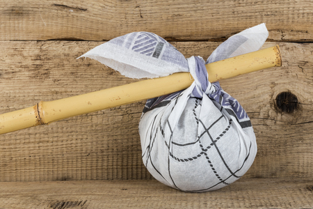 hobo: Rural knapsack on a bamboo pole on a old wooden background