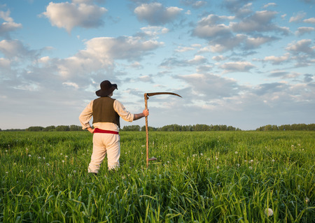 mows: Farmer in a hat  and with a scythe on green field