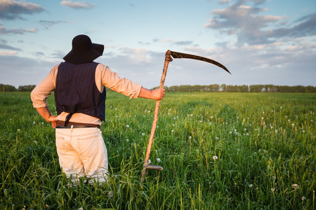 Farmer in a hat and with a scythe on green field Imagens
