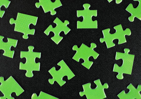 ecomomical: Green puzzles on a black leather background