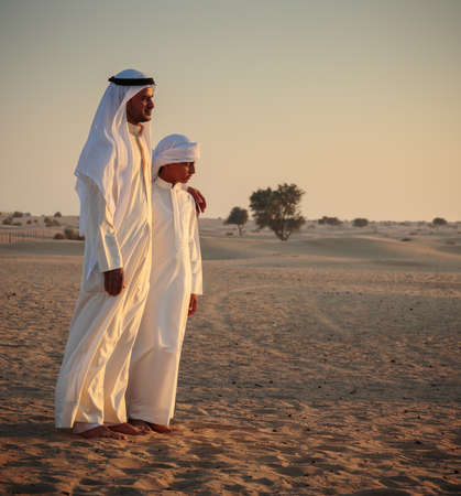 thom: DUBAI, UAE - NOVEMBER 12, 2013: Arab man and a teenager in the desert and watch the sunset