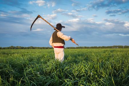 guada�a: Agricultor en un sombrero y con una guada�a en el campo verde