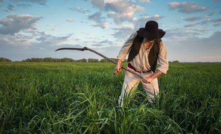ropa vieja: Agricultor de ropa vieja siega la hierba en el campo