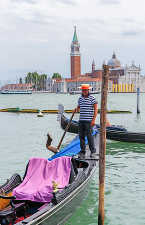 gondolier: VENICE, ITALY - 26 JUNE, 2014: Gondolier rides gondola. The profession of gondolier is controlled by a guild, which issues a limited number of licenses