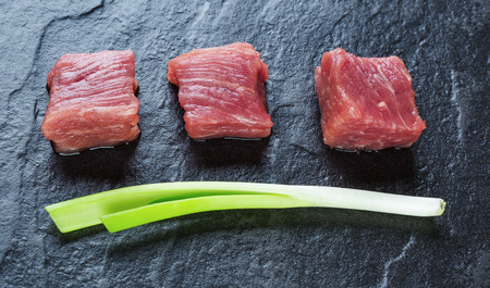 green onions: Three cubes of meat and green onions on the black stone table