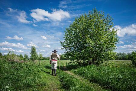 vestidos antiguos: viajero en ropa vieja con una mochila en un camino de campo abandonada