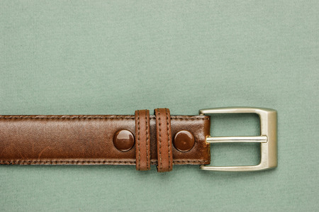 waistband: Old leather belt with a buckle on a green background