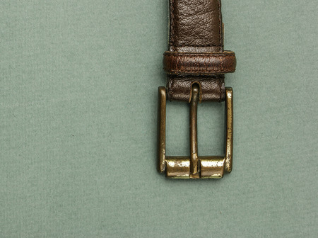 buckle: Old leather belt with a buckle on a green background