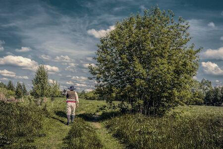 knapsack: Traveler in old clothes with a knapsack  on an abandoned country road. Toned Stock Photo