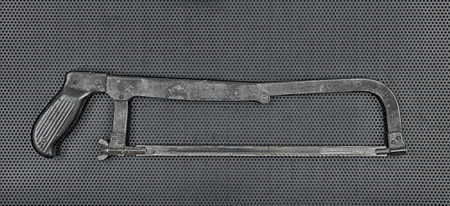 hacksaw: Vintage rusty hacksaw on a metallic background.Toned Stock Photo