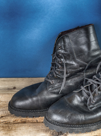 army boots: Black army boots against the wall Stock Photo