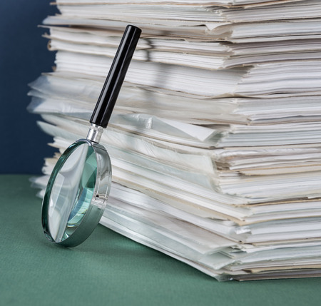 Stack of office folders and magnifying glass Banco de Imagens