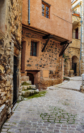 archways: Narrow cobbled street with flowers in the old village Tourrettes-sur-Loup , France. Stock Photo