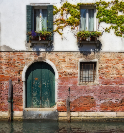romantic places: Facade of an old house on a canal in Venice, Italy