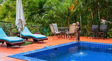 tropez: KOH CHANG, THAILAND - 2 APRIL, 2015: Hotel Saint Tropez. Swimming pool in a tropical garden