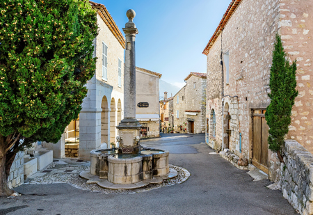 GOURDON, FRANCE - OCTOBER 31, 2014: Medieval street with a fountain in the village