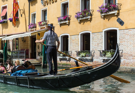 26: VENICE, ITALY - 26 JUNE, 2014: Gondolier rides gondola. The profession of gondolier is controlled by a guild, which issues a limited number of licenses