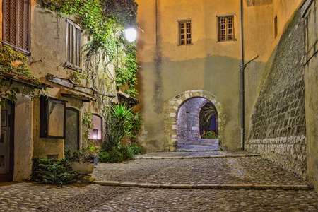 archways: Narrow street in old town in France at night Stock Photo