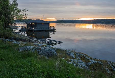 hospedaje: Paisaje con un albergue en el lago en Karelia al atardecer Foto de archivo
