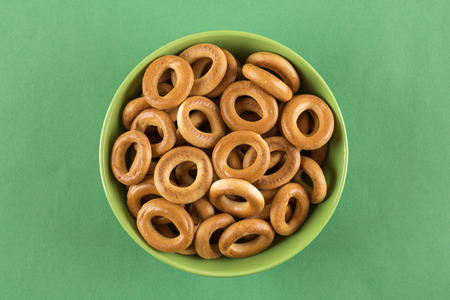 boublik: Bagels in a green bowl on a green background Stock Photo