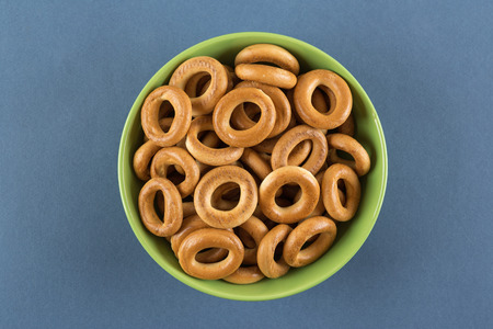 Bagels in a green bowl on a blue background Stock Photo