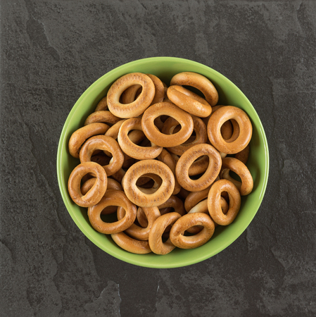 Bagels in a green bowl on the black table