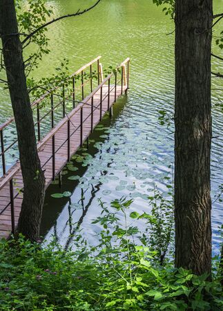 wooden gangway with railings on the lake