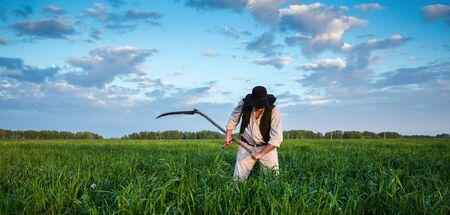 Farmer in old clothes mows grass in the field Stock Photo