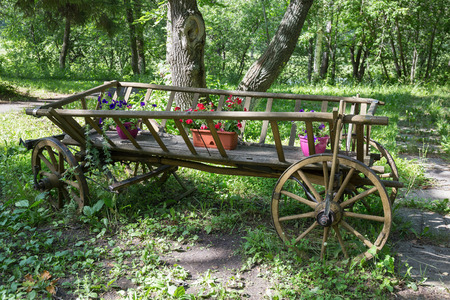 geranium color: Picturesque old wooden cart with flowers in the park Stock Photo