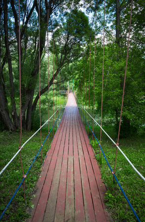 pedestrian bridge: Pedestrian suspension bridge over the river in the forest