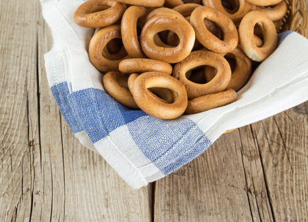 Bagels in a basket with napkin on an old wooden table Stock Photo