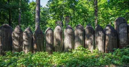 Old wooden fence of sharpened logs in the forest