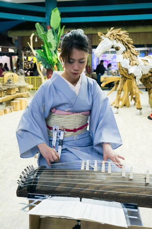 DUBAI, UAE - DECEMBER 4, 2017: Girl is playing a  traditional Japanese plucked instrument koto in the pavilion Japan of Global Village