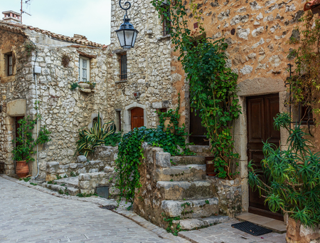 Narrow cobbled street with flowers in the old village Tourrettes-sur-Loup , France. Stockfoto