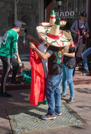 MOSCOW, RUSSIA - June 15, 2018: Football fans with the flag of Mexico on the street in Moscow