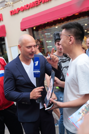 MOSCOW, RUSSIA - June 17, 2018: TV reporters are interviewing Football fans on Nikolskaya street in Moscow during the World Cup Редакционное