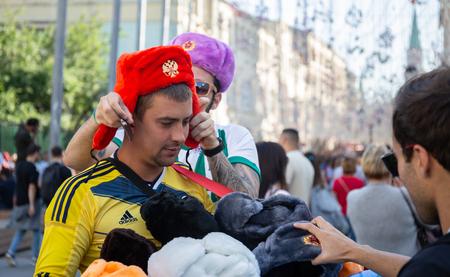 MOSCOW, RUSSIA - June 15, 2018: Football fan in the traditional Russian fur hat on on Nikolskaya street
