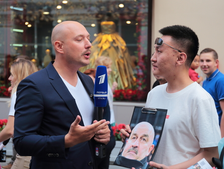 MOSCOW, RUSSIA - June 17, 2018: Football fan with a portrait of the coach of the Russian national team gives interview to the TV reporter on Nikolskaya street  during the World Cup