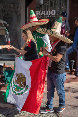 MOSCOW, RUSSIA - June 15, 2018: Football fans with the flag of Mexico on the street in Moscow during the World Cup