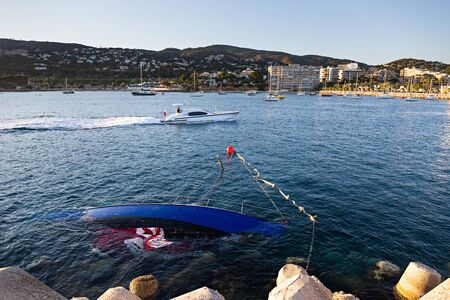 Shipwrecked half-submerged yacht in the calm waters of the Bay of Mallorca
