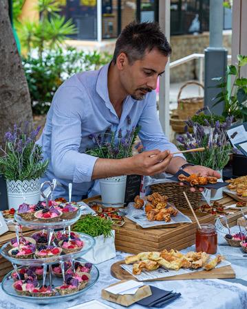 Mallorca, Spain - 26.05.2019: The seller of cakes at the village fair 新聞圖片