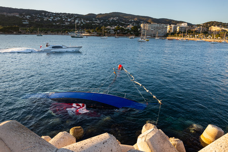 Shipwrecked half-submerged yacht in the calm waters of the Bay of Mallorca, Spain