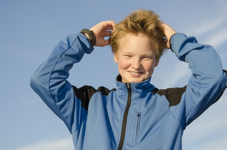 Teenager adjusts his hair against blue sky background Stock Photo - 16716985