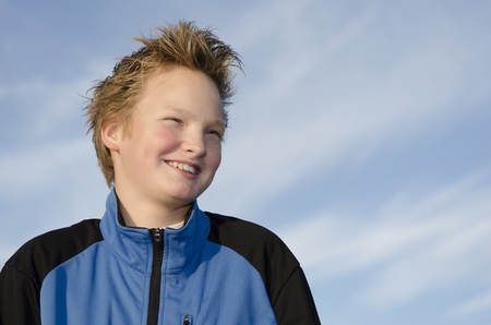 Portrait of happy teen with spiky hairstyle against blue sky Stock Photo - 16716983