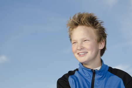 Portrait of happy teenager with spiky hairstyle against sky