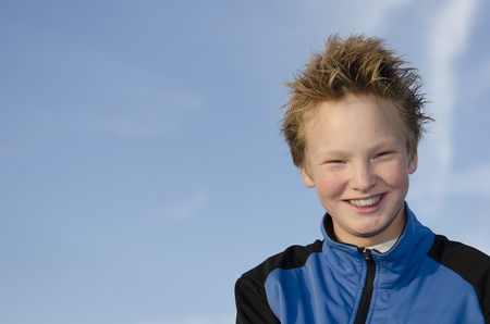 Happy teenager with spiky hair against blue sky background photo