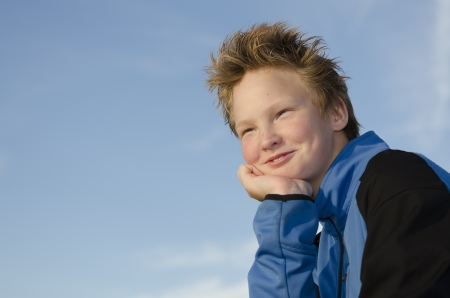 Pleased teen with spiky hairstyle against blue sky background Stock Photo - 16716977