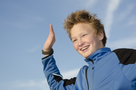 Happy kid with spiky hairstyle joyfully welcome against blue sky Stock Photo - 16716980