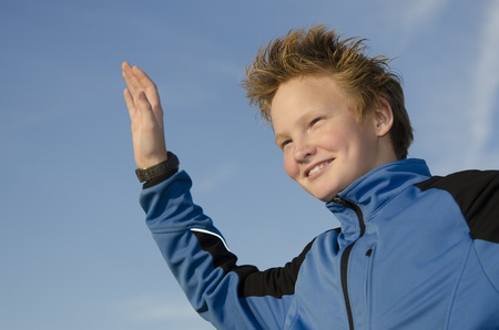 Happy kid with spiky hairstyle joyfully welcome against blue sky Stock Photo